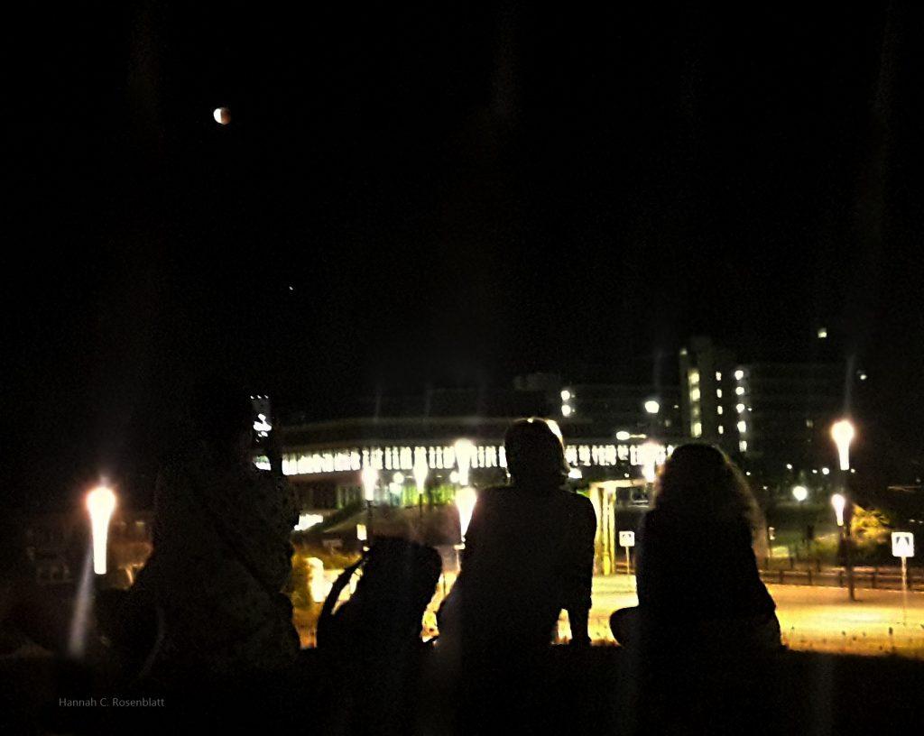 Menschen, die im Gegenlicht eines hell beleuchteten Gebäudekomplexes sitzen. Unscharf ist der noch halbverdeckte Mond mit extras Rot drin zu erkennen.
